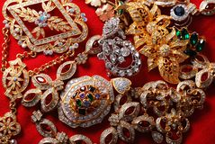 Various jeweleries. Many jeweleries with colorful gems on red cloth Stock Photo