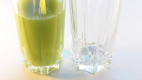 Various juices are poured in two glasses, close can not see the edge. Selective focus. Juices green and orange poured into two glasses, next to no visible edge stock footage