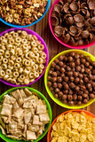 Various kids cereals in plastic bowls Stock Images