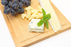 Various kind of cheese and grape on a cutting board Stock Image