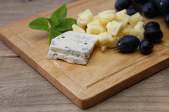 Various kind of cheese and grape on a cutting board Royalty Free Stock Photos