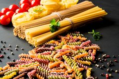 Various kind of italian raw Pasta. colorful fusilli pasta, spaghetti, fettuccine with tomatos on a black background. Closeup Royalty Free Stock Image