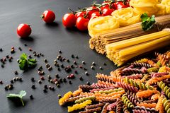 Various kind of italian raw Pasta. colorful fusilli pasta, spaghetti, fettuccine with tomatos on a black background. Closeup Royalty Free Stock Photo
