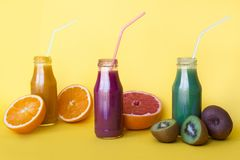 Various kind of smoothies or juices in bottles, healthy diet food concept on yellow. stock image
