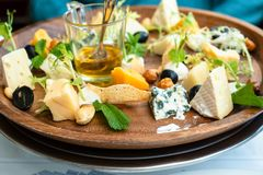 Various kinds of cheeses and honey on plate royalty free stock photos