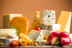 Various Kinds of Cheeses on the Wooden Platter -. Wooden board wood cheese various yellow background Stock Image
