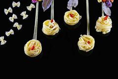 Various kinds of colored raw Italian pasta on a black background, top view, in the form of flower fields and butterflies from food Royalty Free Stock Images