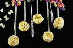 Various kinds of colored raw Italian pasta, wheat stems on a black background, top view, in the form of flower fields and butterfl Stock Photography
