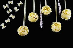 Various kinds of colored raw Italian pasta, wheat stems on a black background, top view, in the form of flower fields and butterfl Royalty Free Stock Photo