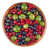Various kinds of fresh berries in a wooden bowl on a white Royalty Free Stock Image
