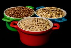 Various kinds of healthy food. Pearl barley, buckwheat and oat flakes isolated on black background Stock Images