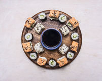 Various kinds of sushi, laid out on a wooden round tray, lined with a circle around the soy sauce  Asian food on wooden rustic bac Stock Images