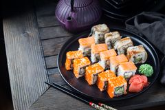 Various kinds of sushi. Rolls served on black plate over dark background royalty free stock photos