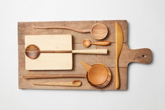Various kitchen utensil on white wooden background. Cutting board, fork, knife and spoon Stock Images