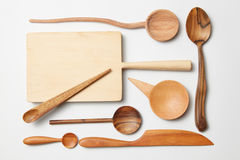 Various kitchen utensil on white wooden background. Cutting board, fork, knife and spoon Royalty Free Stock Photography