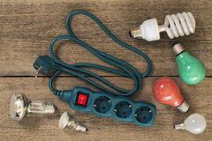 Various lamps and multi-outlet  extension cord. On a wooden table Stock Photos