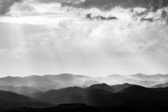 Various layers of hills and mountains with mist between them, wi. Th sun rays coming out through the clouds royalty free stock photos