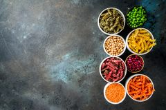 Various legume pasta. Trend healthy food, vegan diet concept. Multi colored legume pasta with raw beans. Beans, chickpeas, green peas, lentils. Copy space top royalty free stock photography