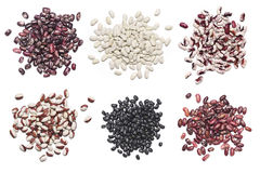 Various legume set. Piles of various legume grains isolated on white background: white, black, purple and red speckled beans Stock Photo