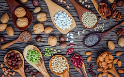 Various legumes and different kinds of nutshells in spoons. Waln Royalty Free Stock Photography