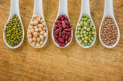 Various legumes on spoons Royalty Free Stock Images