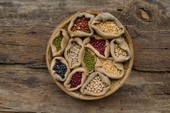 Various legumes in wooden weave bamboo basket top view. Various legumes in wooden weave bamboo basket on wooden background, top view Stock Images