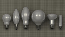 Various light bulbs. Various white glossy light bulbs lying on gray squared background, front view Stock Images