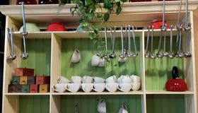 Various lovely accessories standing on shelf and cupboard in cozy kitchen. Kitchenware keeping. Kitchen shelf with royalty free stock photo
