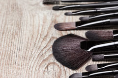 Various makeup brushes on shabby wooden surface Royalty Free Stock Images