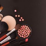 Various makeup products on dark black background with copyspace Royalty Free Stock Image