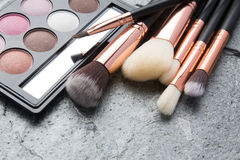 Various makeup products on dark stone. Background Royalty Free Stock Photo