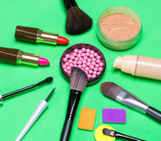 Various makeup products on green background Royalty Free Stock Photo