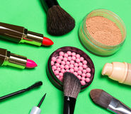 Various makeup products on green background. Various makeup products: jar with shimmer blush balls surrounded by cream foundation bottle, jar of loose powder Stock Photos