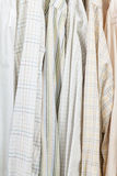 Various male shirts on hangers in wardrobe. Close up Royalty Free Stock Photography