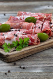 Various meats on serving board with rustic background Stock Photos