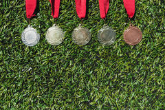 Various medals lying on soccer pitch. Top view of various medals lying on soccer pitch Royalty Free Stock Images