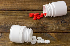 Various medical apothecary bottles with colorful pills. Various medical pill bottles on a wooden background stock images