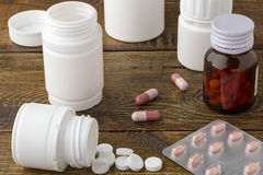Various medical apothecary pill bottles. Various medical pill bottles on a wooden background royalty free stock photos