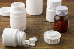 Various medical apothecary pill bottles. Various medical pill bottles on a wooden background royalty free stock image