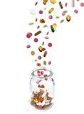 Various medical pills falling into glass jar Stock Photos