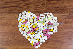 Various medications are laid out on the table in the shape of a heart. Royalty Free Stock Image