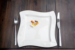 Various pills are on white plates on a brown table royalty free stock images
