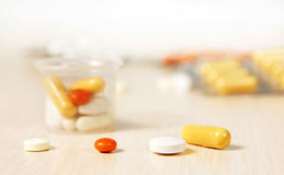 Various medicine tablets and pills in a plastic little glass Stock Photos