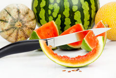 Various melons and pieces with a kitchen knife Royalty Free Stock Photos