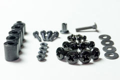 Various metal bolts, nuts, washers lie next to each other on a w Stock Images