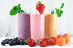 Various milkshakes with fruits. Three various protein milkshakes in glasses with fruits on rustic white wooden background stock photography