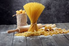 Various mix of pasta on grey rustic background. Diet and food co. Various mix of pasta on grey rustic background. Making homemade pasta Royalty Free Stock Photo