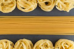 Various mix of pasta raw closeup background. Delicious dry uncooked ingredient for traditional Italian cuisine dish Stock Photos