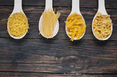 Various mix of pasta on wooden rustic background, sack and spoons Stock Images