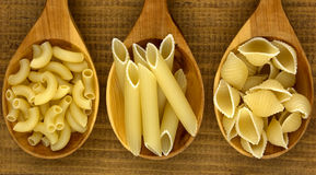 Various mix of pasta on wooden rustic background and wooden spoo royalty free stock image
